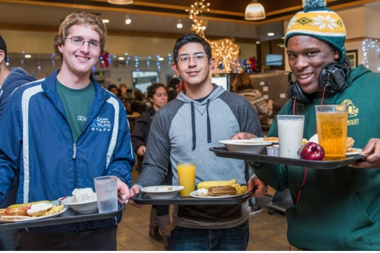 three students with breakfast trays full of food